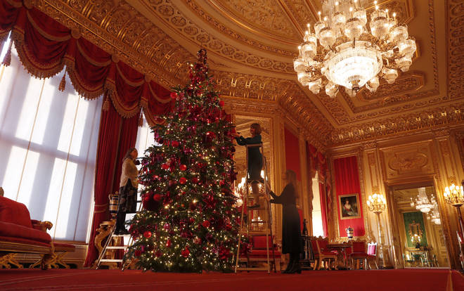 Staff decorate one of the Queen's huge trees