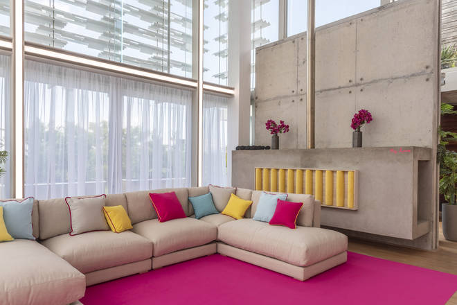 The communal area features a large sofa for the islanders to relax on