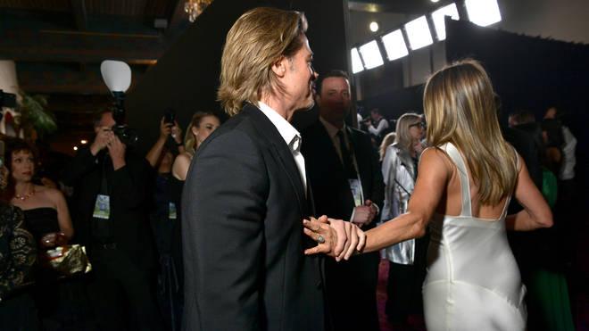 Brad was seen clutching Jennifer's hand as she walked away