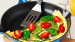Omelette with green bean. spinach and tomato in a skillet.