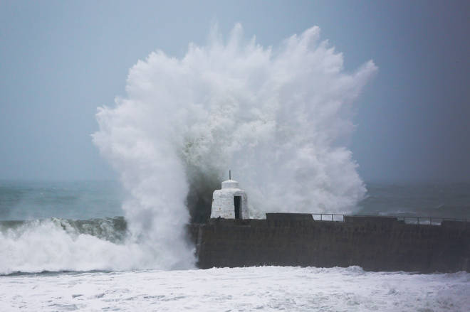 Waves pound against the harbour wall at Portreath, Cornwall.