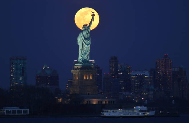 The worm moon lit up New York City and the Statue Of Liberty on Monday night