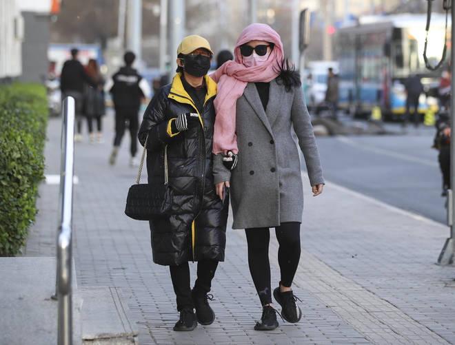 Two women walk down the street in Beijing