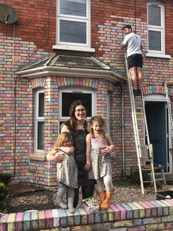 Fern, Marco and their two daughters stand proudly by their rainbow house