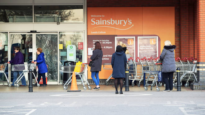 Sainsbury's observing a two-metre distance while queuing to get into Sainsbury's