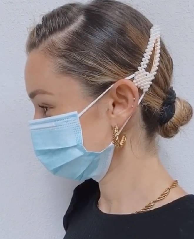 The hairdresser used a pearl clip to bring the mask strings back from the ears