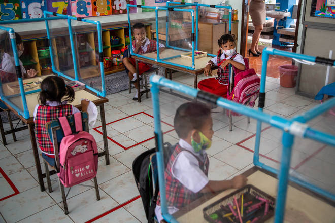 The children sit in separate pods in the classrooms