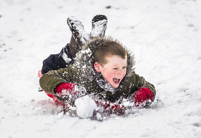 A boy enjoys the snow in the UK last year