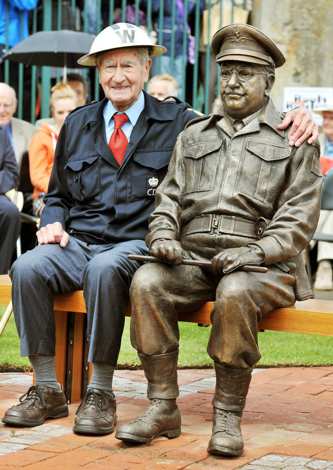 Bill Pertwee who starred in the classic TV comedy Dad's Army sits beside at bronze statue of Capatin Mainwaring played by actor Arthur Lowe.