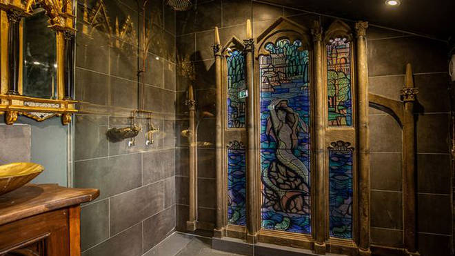 The bathroom has a huge stained glass window