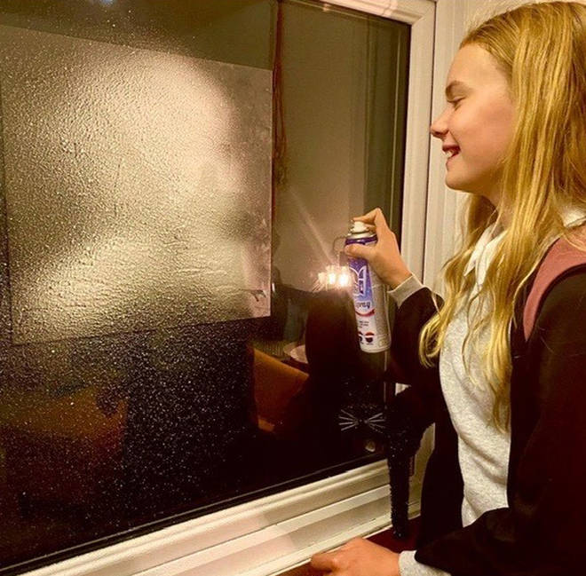 Gently stick the stencil to the window and spray the fake snow