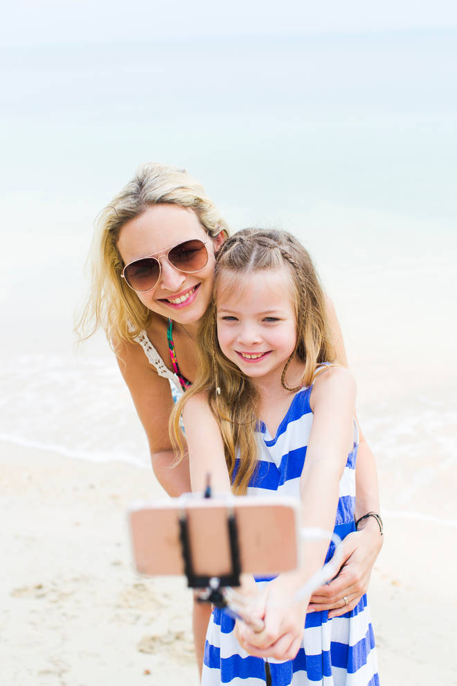 Smiling Girl Taking Selfie With Mother At Beach