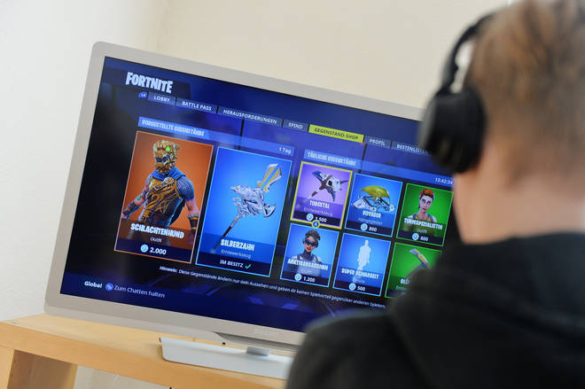 A boy plays Fortnite on his games console