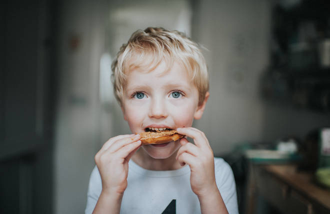 A child eating a peanut bagel