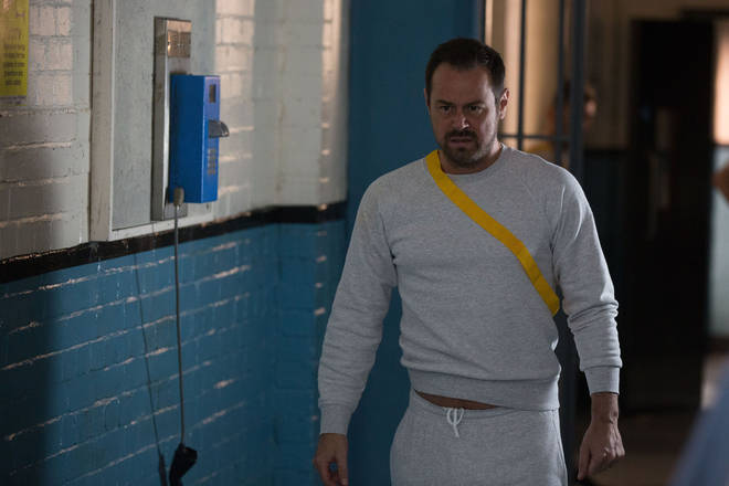 Mick Carter walks angrily through the prison in EastEnders