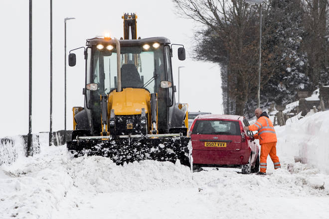 A car receives help from a gritter as it gets stuck in snow