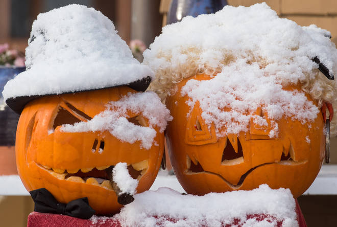 Two pumpkins covered in snow