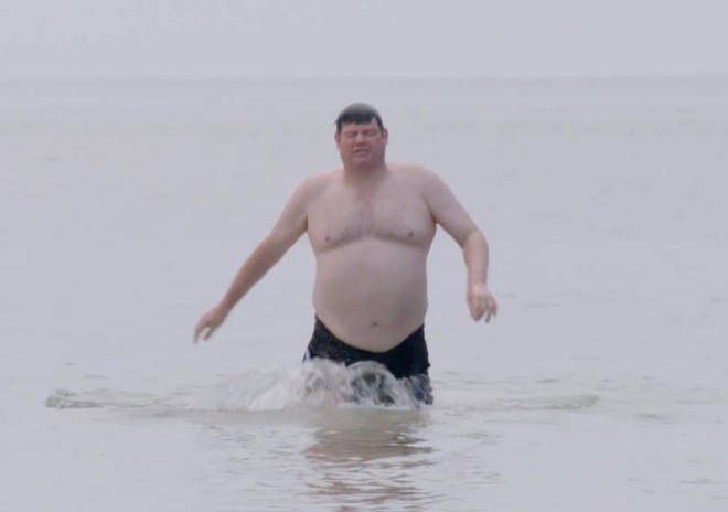 Mark Labbett is seen walking out the sea in the clip