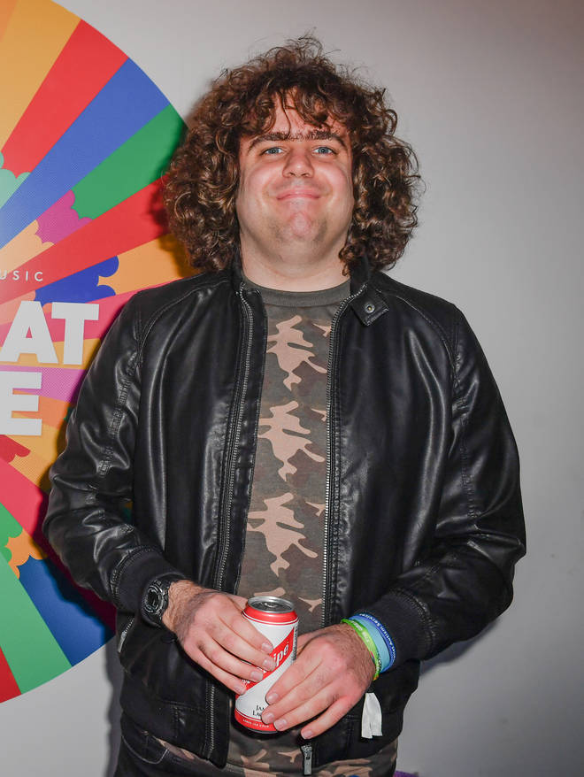 Daniel Wakeford smiles in a camouflage t-shirt and leather jacket