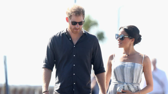 Prince Harry and Meghan Markle holding hands on on royal tour