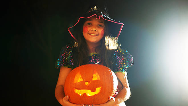 Girl wearing a witch outfit holding a pumpkin