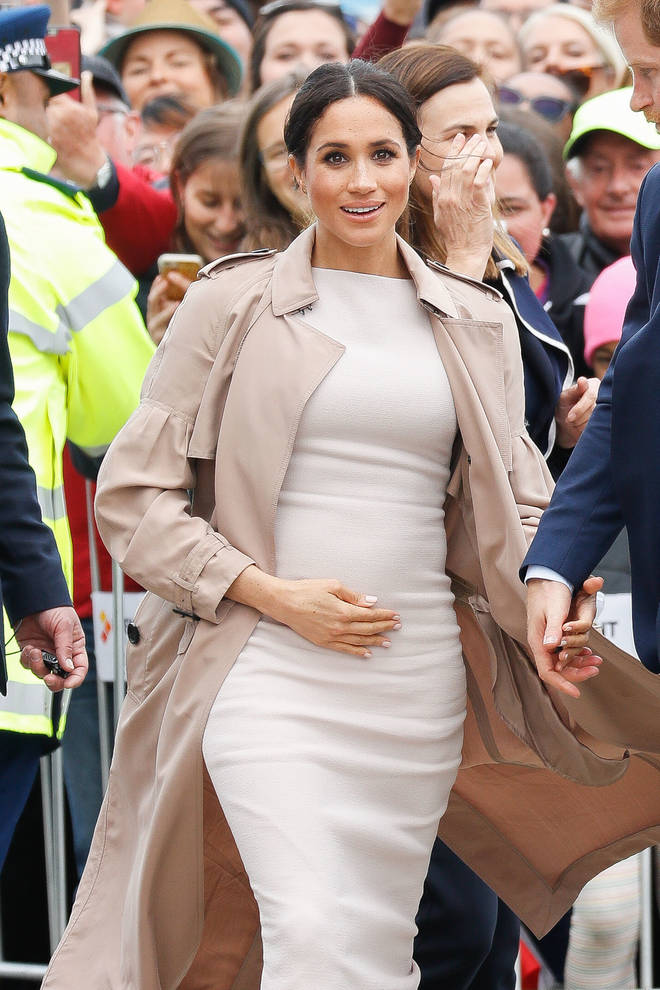 Meghan Markle cradles her baby bump on the royal tour
