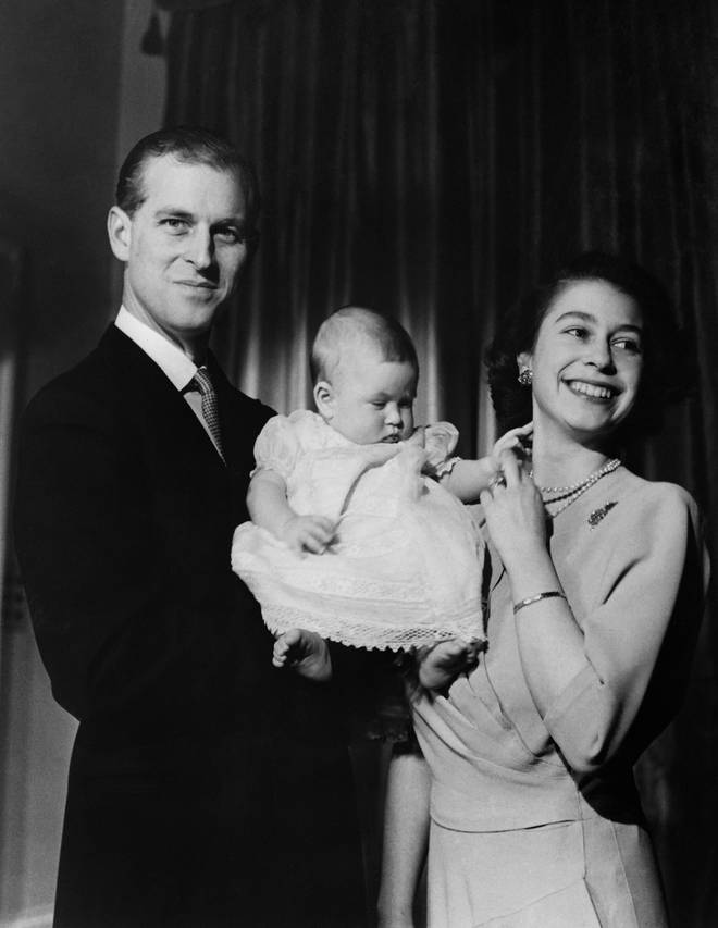 Prince Philip and the Queen pose with their son Prince Charles in 1949