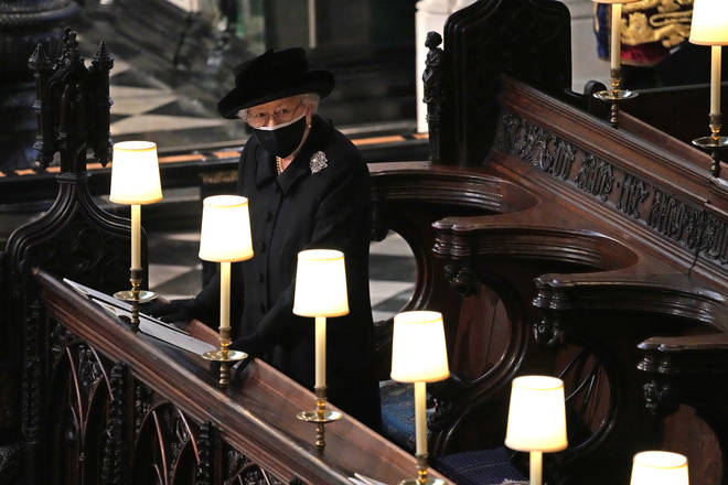 The Queen watches as Prince Philip's coffin enters St George's Chapel
