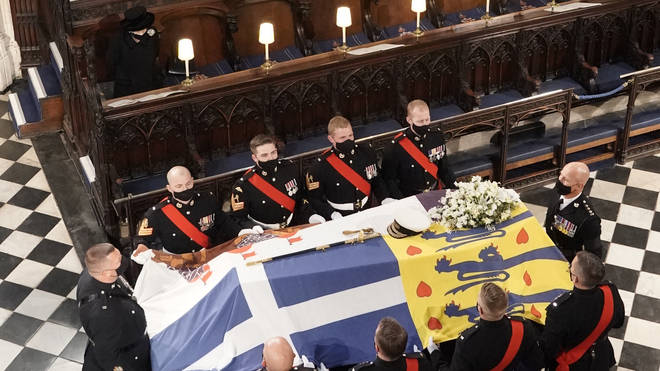 The Queen stands as the coffin is carried into the Chapel