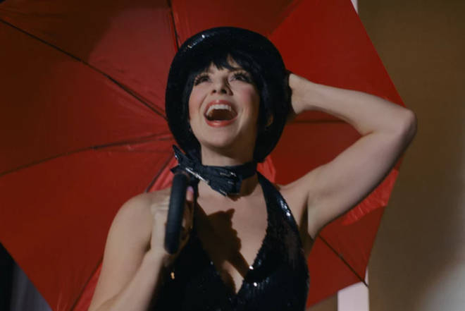 Liza is played by Krysta Rodriguez in Halston