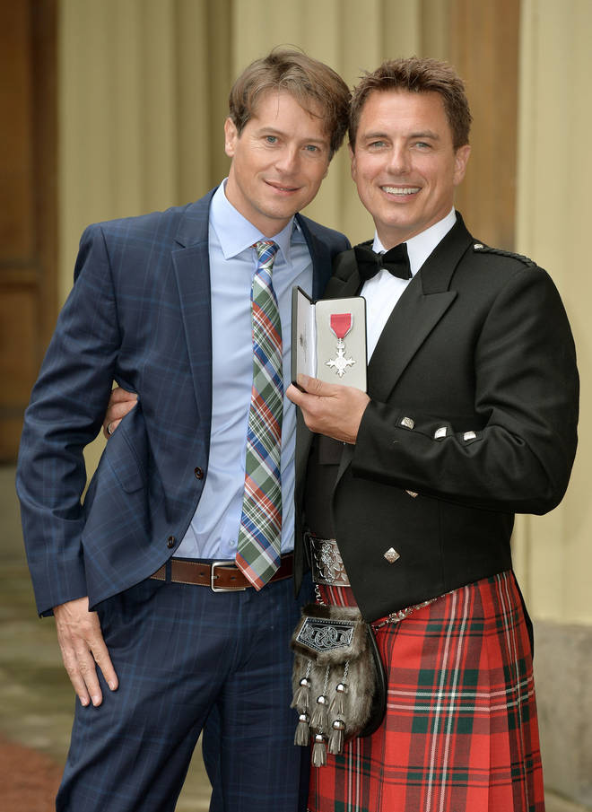 John poses with husband Scott Gill after being awarded an MBE