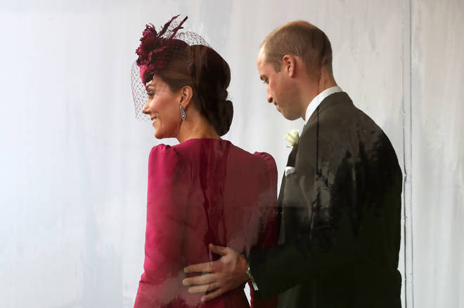 William places a hand on the back of his wife as they leave the wedding of Princess Eugenie and Jack Brooksbank