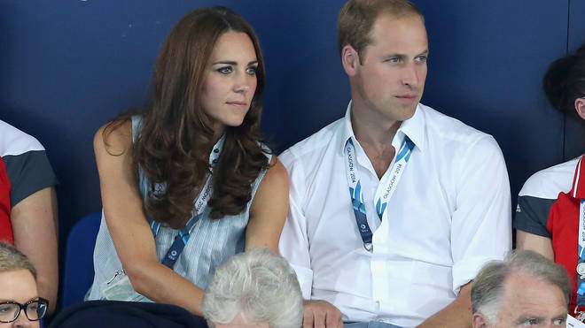 Kate and William hold hands as they watch swimming together