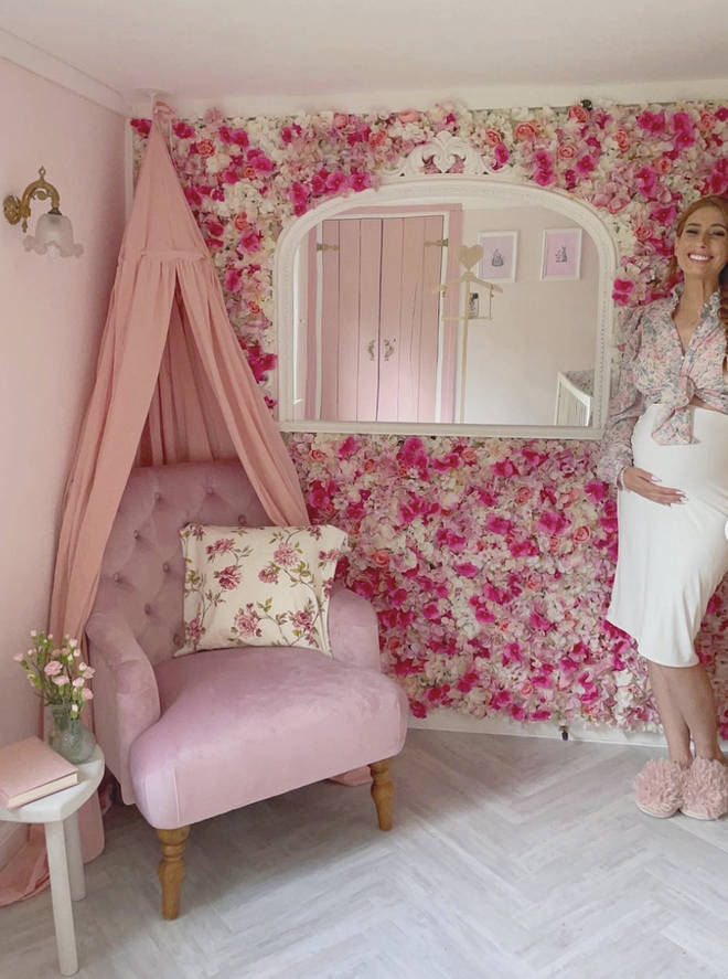 The nursery features a stunning pink flower wall