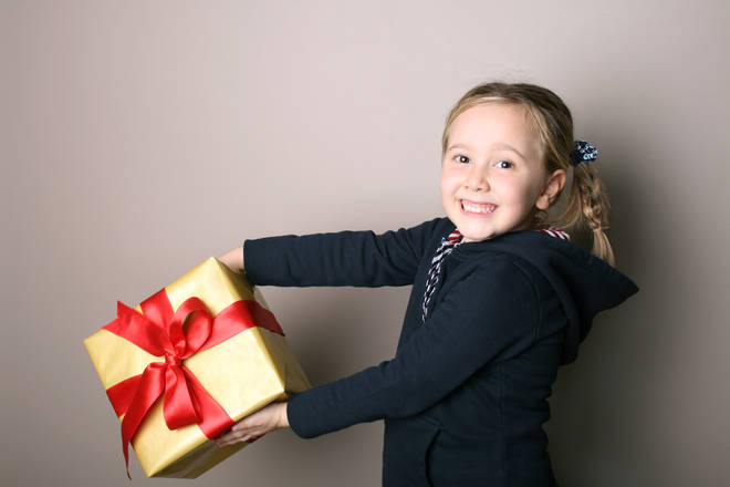 School child holding a Christmas present