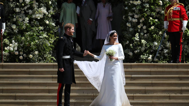 Meghan Markle and Prince Harry smile for cameras following their wedding at Windsor Castle