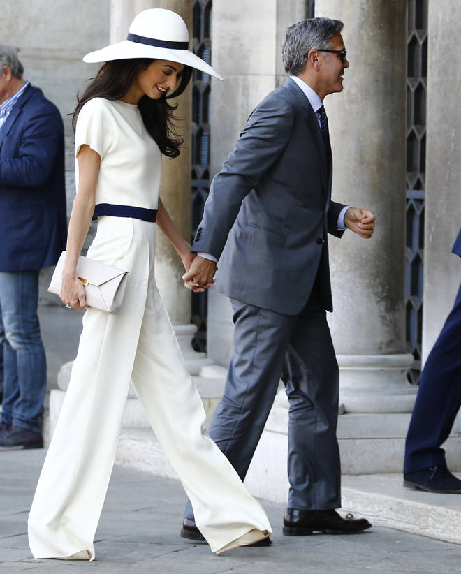 Amal and George Clooney hold hands on their way to their civil ceremony in Italy