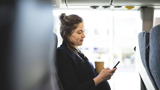 Pregnant woman enjoys a coffee on the train