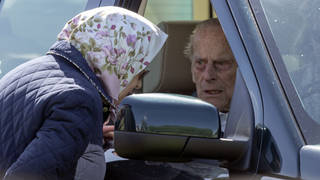 Prince Philip pictured in his Land Rover speaking to the Queen