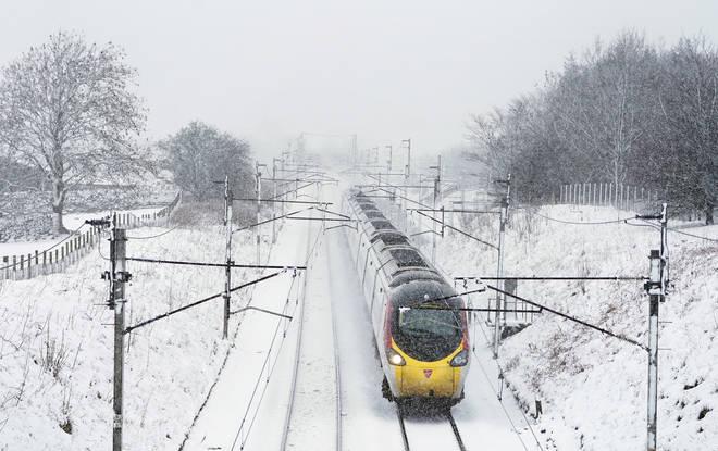 A Virgin Train makes its way through snow towards London