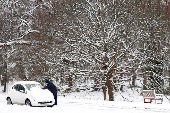 A man sweeping the snow off his car this morning