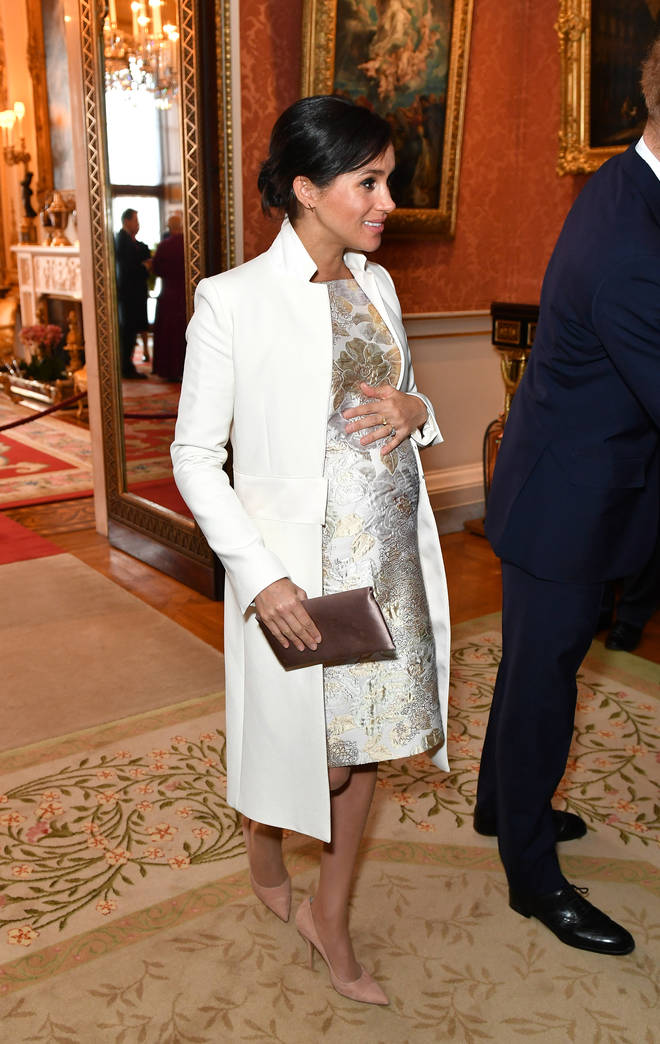 Meghan Markle cradled her baby bump as she arrived