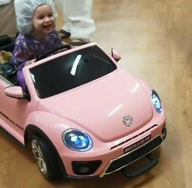 Girl in pink hospital car
