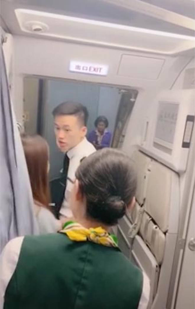 The plan e was delayed after a woman allegedly stopped cabin crew from shutting the doors