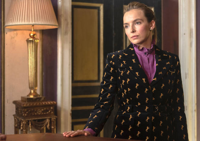 Villanelle in a purple blouse and patterned blazer