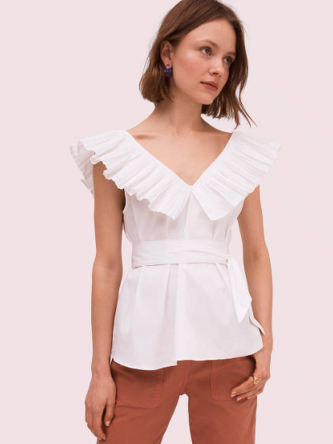 Holly's white blouse is from Kate Spade
