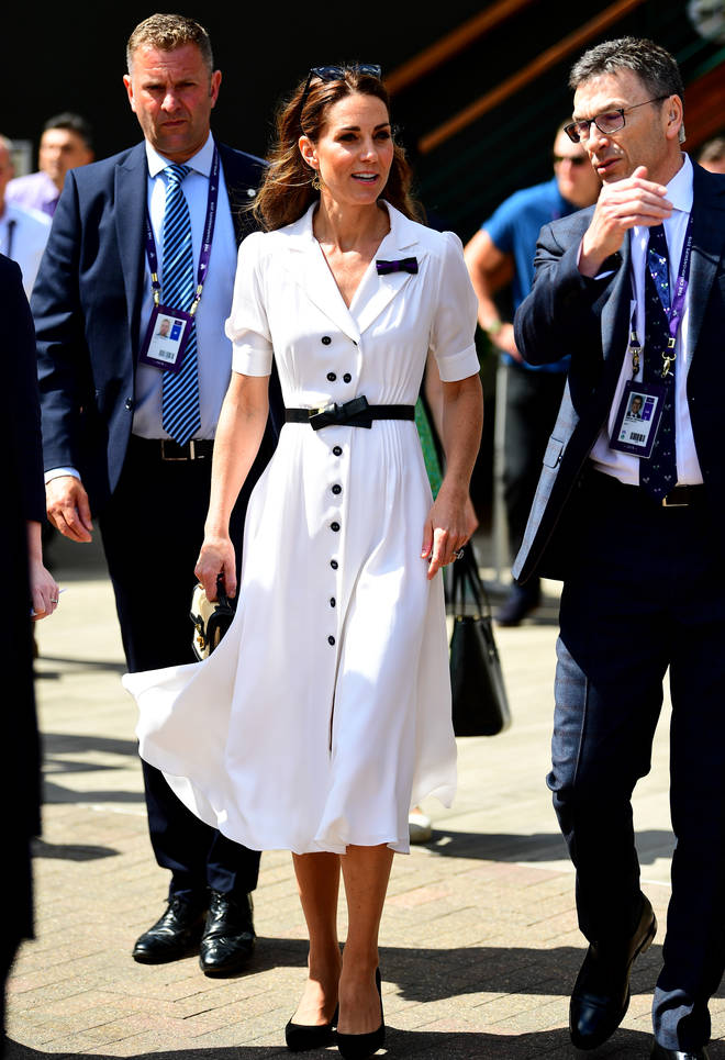 Kate Middleton is wearing a classic white tea dress, with black bow belt and court shoes