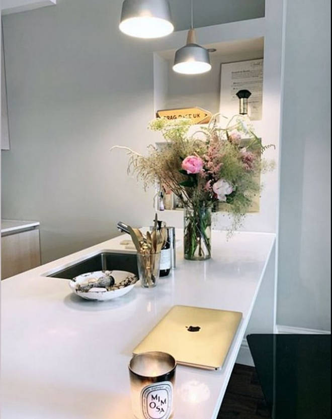 The stunning white kitchen has a bunch of fresh flowers and a Diptyque candle