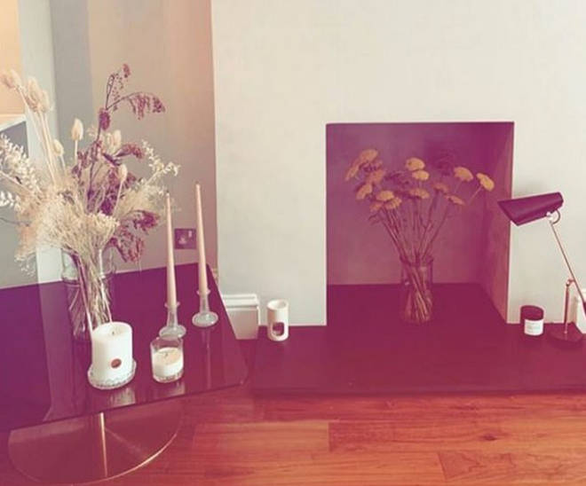 There's a gorgeous fireplace in the new property which has been filled with more flowers and plenty of candles decorate the new pad
