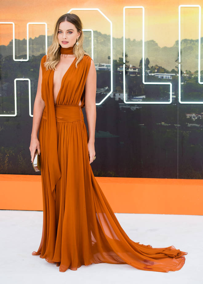 Margot Robbie dressed in a burnt orange gown for the premiere